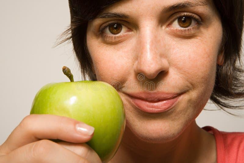 Kvinnainnehav ett äpple royaltyfri fotografi