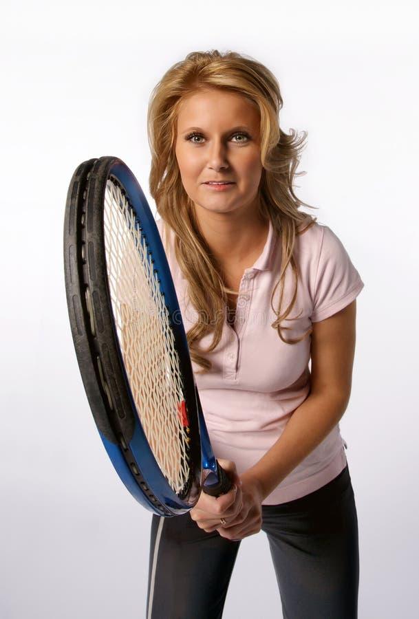 Kvinnainnehav ett tennisracket arkivfoton
