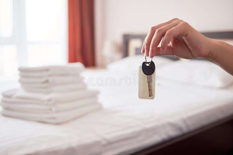 Kvinnainnehav i handrumtangent med den tomma etiketten på hotellföljet, kopieringsutrymme Sovruminre i suddighet arkivfoto
