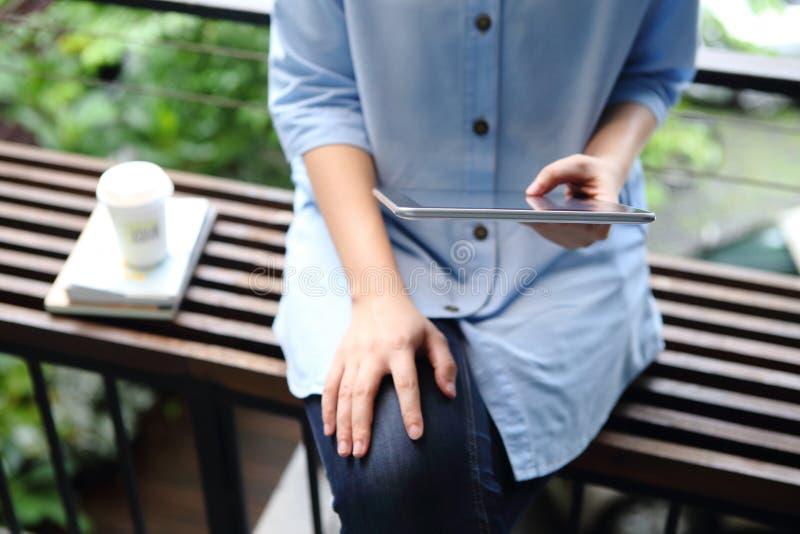 Kvinnainnehav och användaminnestavla med böcker och kaffekoppen på offi royaltyfri fotografi