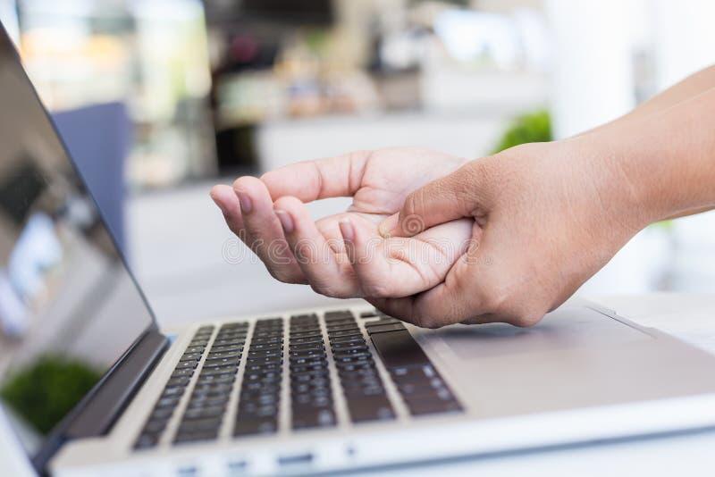 Kvinnainnehav och trängande eller trycka på hennes hand, medan arbeta wi royaltyfri foto