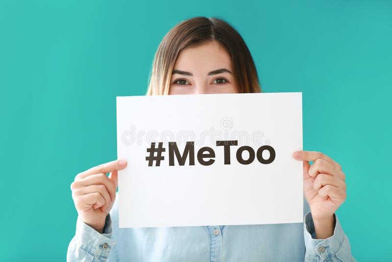 Kvinnainnehavark av papper med hashtag som är meToo på färgbakgrund royaltyfri bild