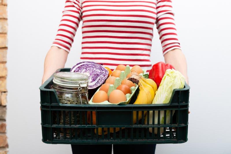 Kvinnainnehavask av livsmedelsbutikmat och från lager Online-begrepp för service för livsmedelsbutikshopping royaltyfri bild