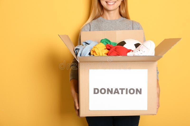 Kvinnainnehavask med donationer på färgbakgrund royaltyfria bilder