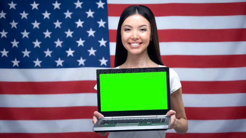 Kvinnainnehavbärbar dator med den gröna skärmen, USA flagga på bakgrund, språkkurser royaltyfri bild