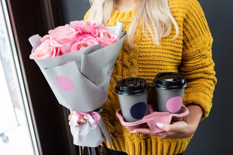 Kvinnainnehavbehållare för kaffe som går, och blommor royaltyfria bilder