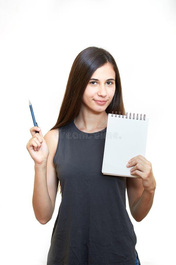 Kvinnainnehavblyertspenna med anteckningsboken och se upp isolerat på a royaltyfri bild
