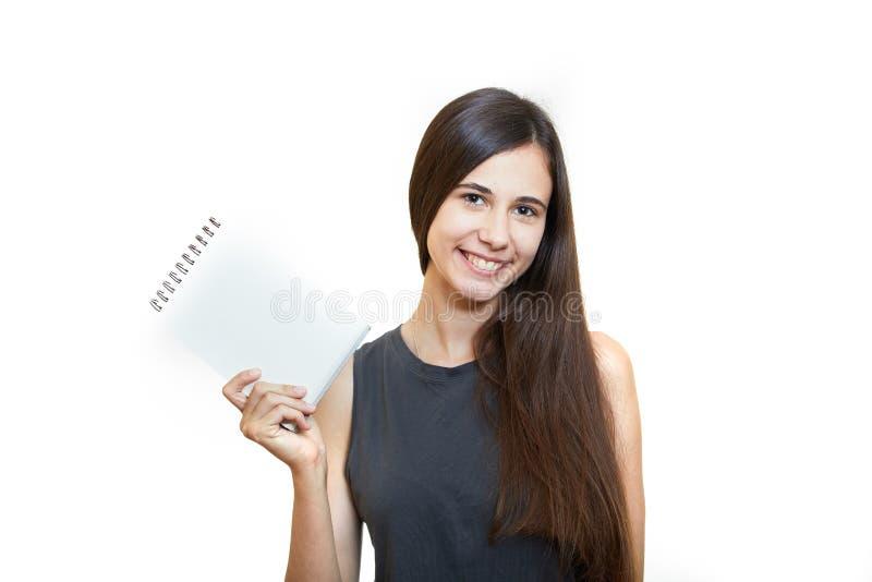 Kvinnainnehavblyertspenna med anteckningsboken och se upp isolerat på a arkivbilder