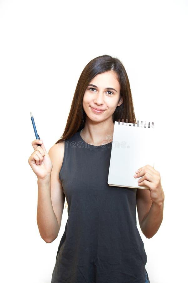 Kvinnainnehavblyertspenna med anteckningsboken och se upp isolerat på en vit bakgrund arkivbilder