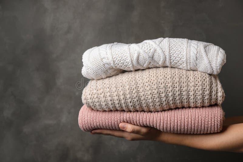 Kvinnainnehavbunt av vikta varma stack tröjor royaltyfri bild