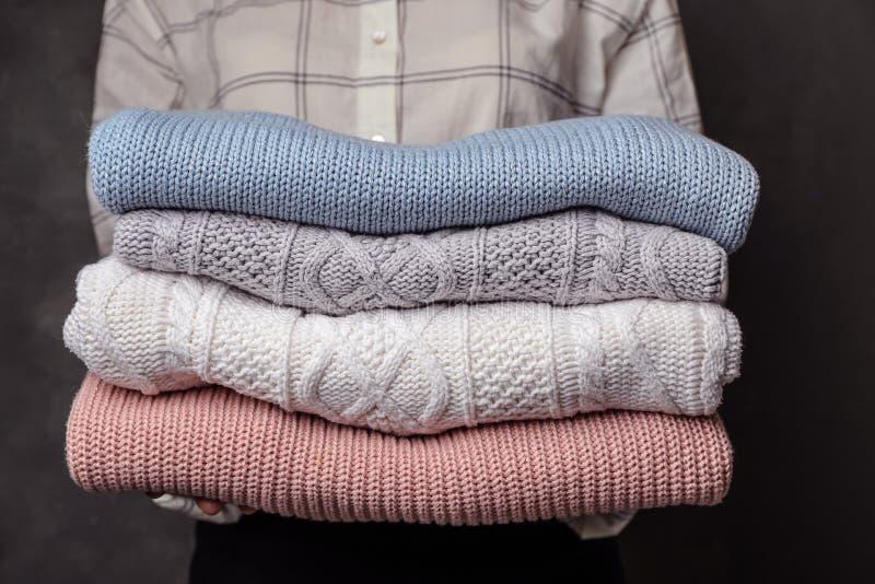 Kvinnainnehavbunt av vikta varma stack tröjor royaltyfri fotografi
