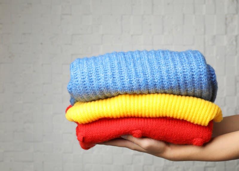 Kvinnainnehavbunt av vikta varma stack tröjor arkivbild