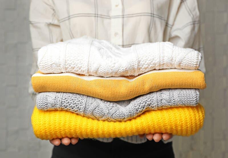 Kvinnainnehavbunt av vikta varma stack tröjor royaltyfria bilder