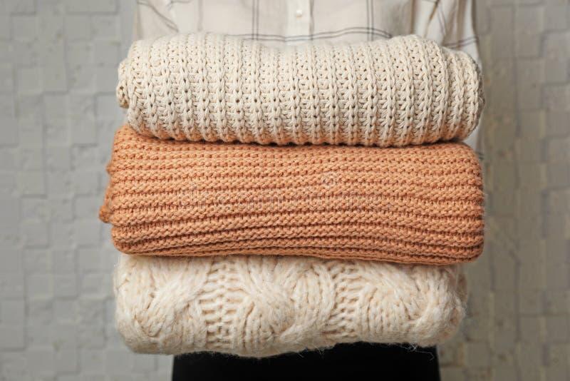 Kvinnainnehavbunt av vikta varma stack tröjor fotografering för bildbyråer