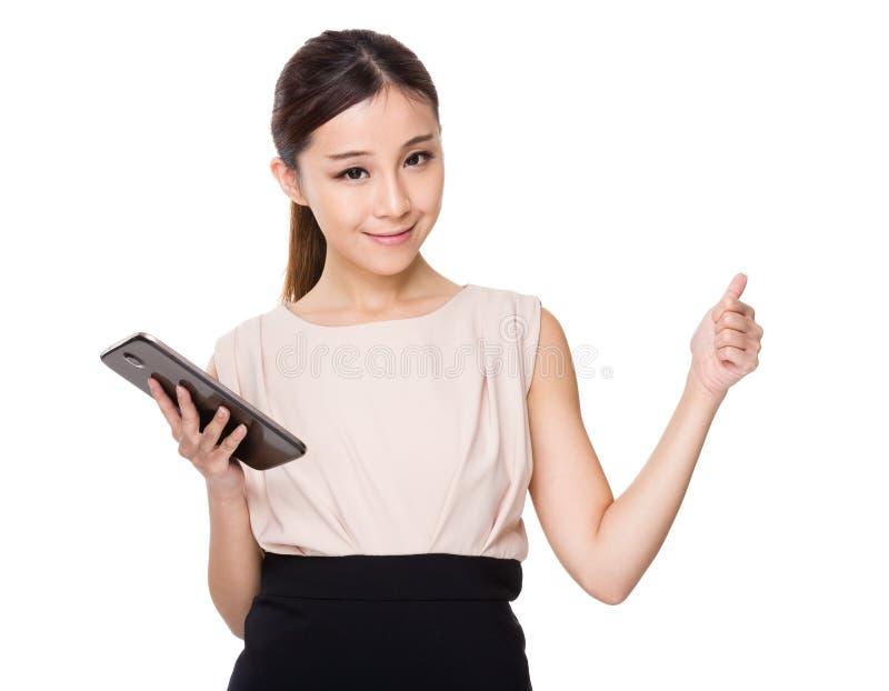 Kvinnainnehavet med den digitala minnestavlan och tummen gör en gest upp royaltyfri bild