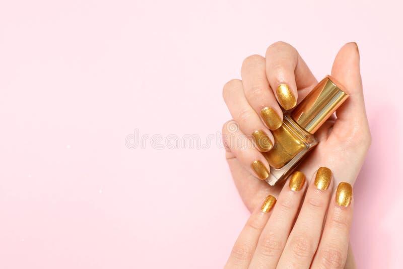 Kvinnainnehavflaskan av guld- spikar polermedel i manicured hand på färgbakgrund, bästa sikt fotografering för bildbyråer