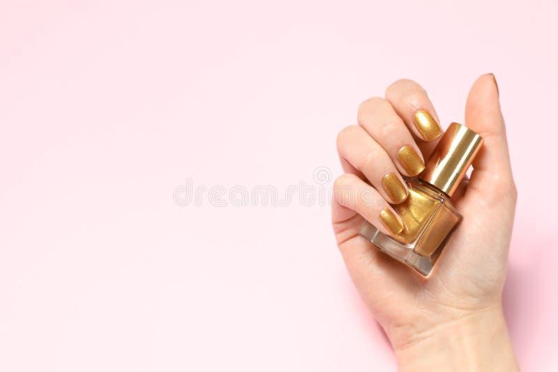 Kvinnainnehavflaskan av guld- spikar polermedel i manicured hand på färgbakgrund, bästa sikt arkivfoto