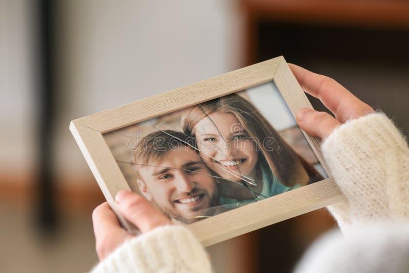 Kvinnainnehavfoto av lyckliga par i ram med sprucket exponeringsglas, closeup Begrepp av skilsm?ssan arkivfoto