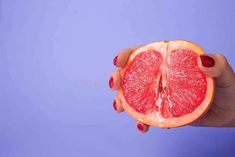 Kvinnainnehavhalva av den saftiga grapefrukten på färgbakgrund Erotiskt begrepp arkivbild