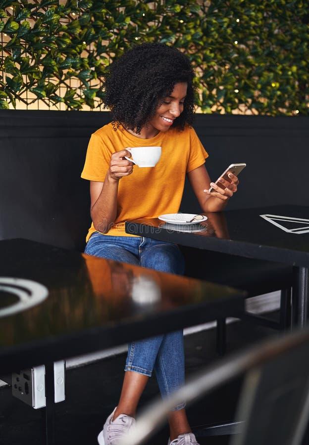 Kvinnainnehavkopp kaffe genom att använda mobiltelefonen i kafé arkivbild