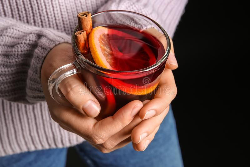 Kvinnainnehavkopp med varmt funderat vin mot mörk bakgrund royaltyfri fotografi