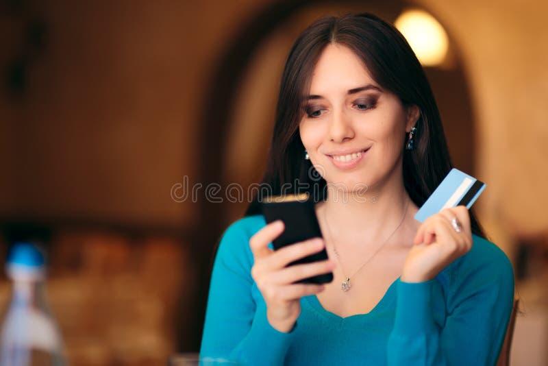 Kvinnainnehavkreditkort och Smartphone som direktanslutet shoppar fotografering för bildbyråer
