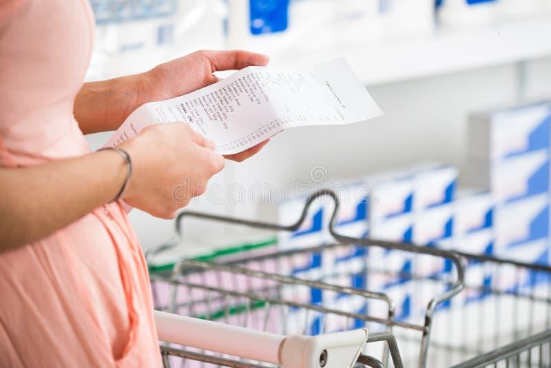 Kvinnainnehavkvitto i supermarket royaltyfria foton