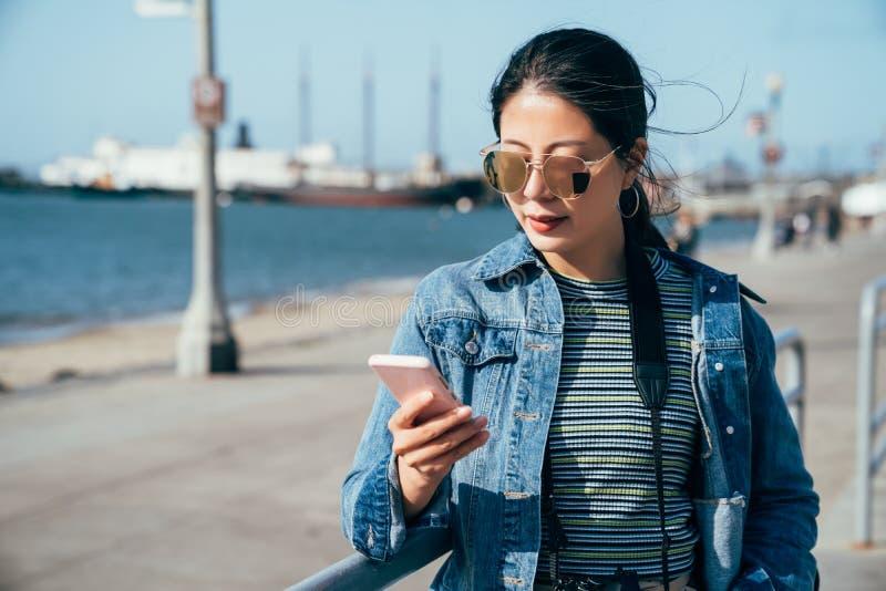 Kvinnainnehavmobiltelefon som söker online-översikten royaltyfria foton