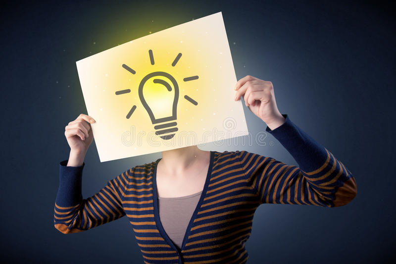 Kvinnainnehavpapper med lightbulben fotografering för bildbyråer