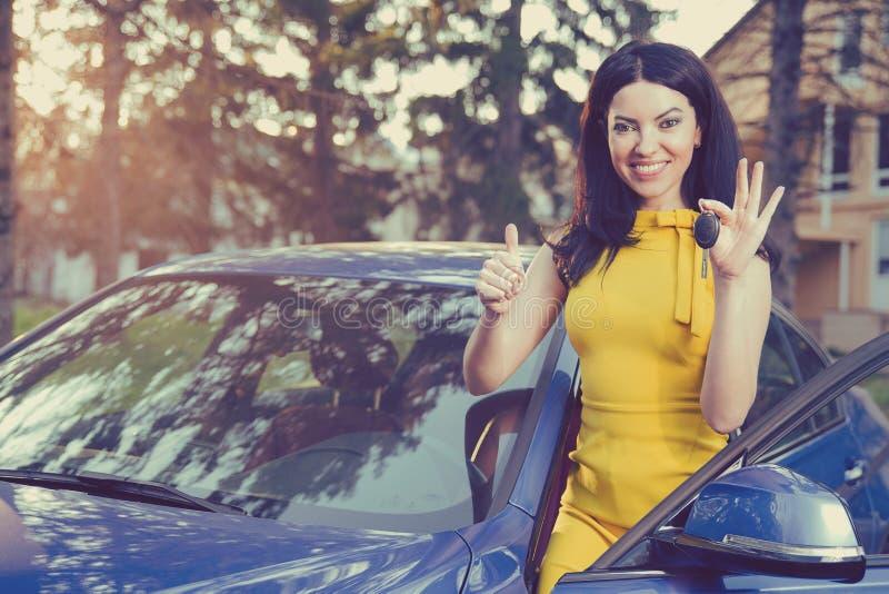 Kvinnainnehavtangenter till den nya bilen som ler visningtummar upp på en bakgrund av ett hus royaltyfri bild
