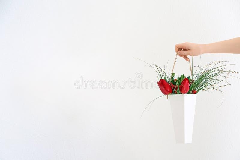 Kvinnainnehavvas med den härliga buketten av blommor som gåvan på ljus bakgrund fotografering för bildbyråer