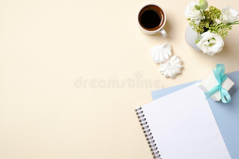 Kvinnainrikesdepartementetskrivbord med den tomma pappers- notepaden, kaffekoppen, gåvaasken, blommabuketten och kvinnlig modetil arkivbild