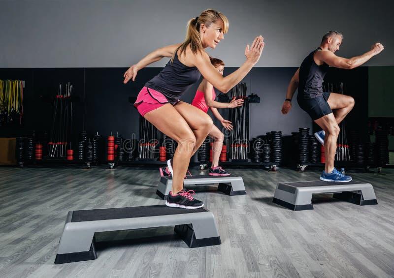 Kvinnainstruktör som gör aerobisk grupp med steppers in arkivbild