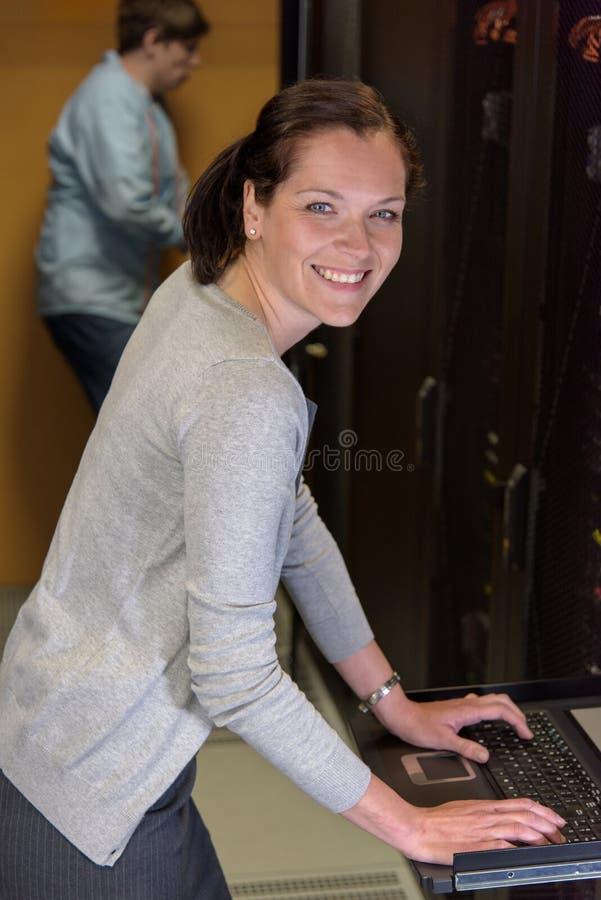 KvinnaIT-tekniker i serverrum arkivfoto