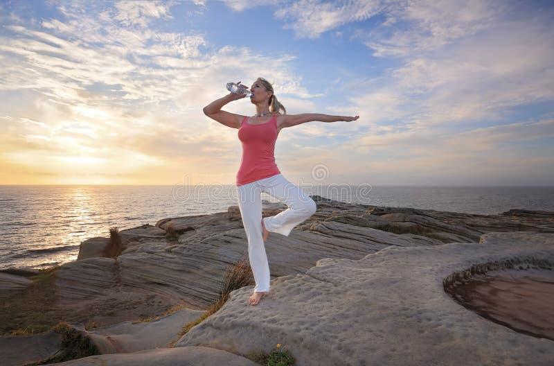 Kvinnajämvikt som dricker wqter under övning arkivfoton