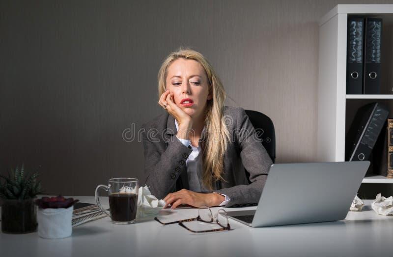 Kvinnakänsla som borras på hennes jobb royaltyfri foto