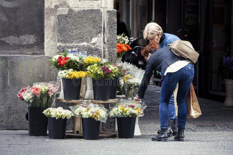 Kvinnaköpande blommar från gatuförsäljare royaltyfri foto