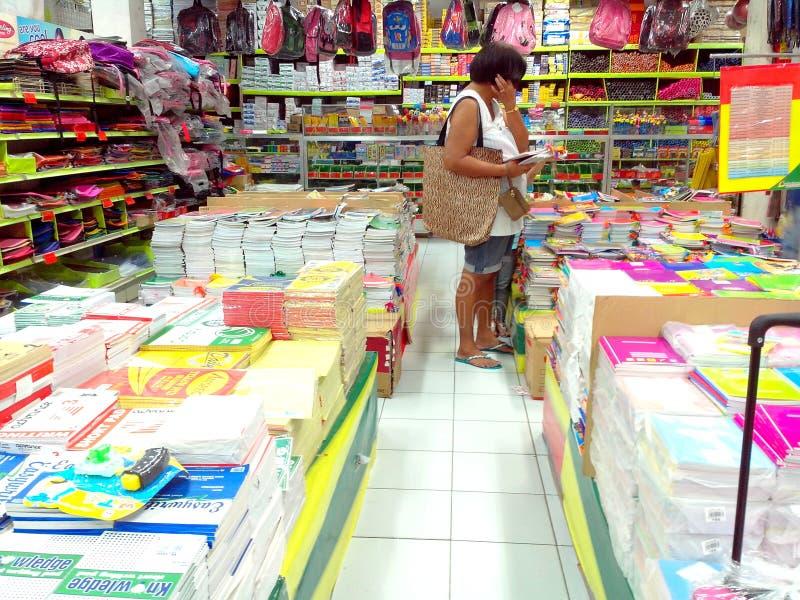Kvinnaköpande eller shopping för skolatillförsel arkivfoton