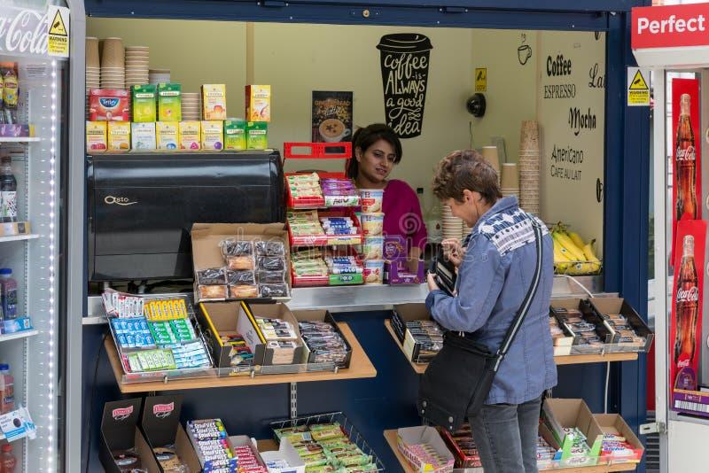 Kvinnaköpandesötsaker i kioskjärnvägsstation nära Windsor Castle royaltyfria bilder