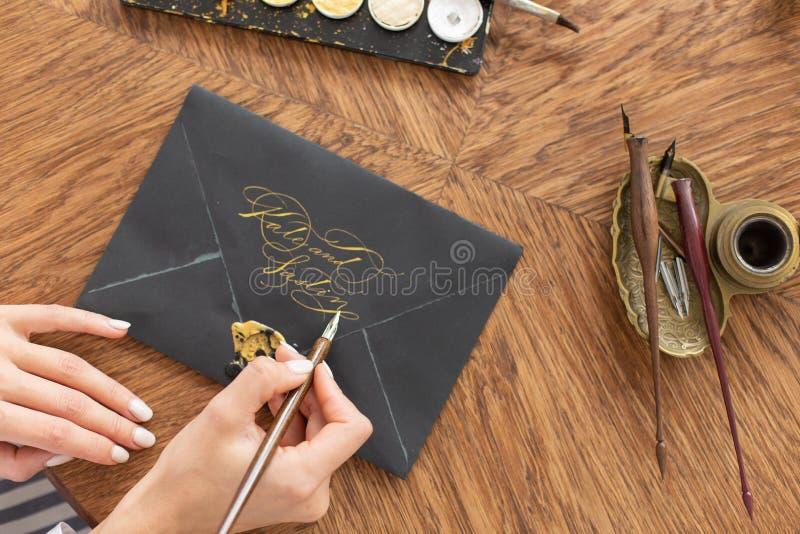 Kvinnakalligrafen rymmer en penna med färgpulver och tecken en bokstav i handskriven stilsort N?rbild slapp fokus Top besk?dar arkivfoto