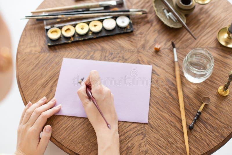 Kvinnakalligrafen rymmer en penna med färgpulver och tecken en bokstav i handskriven stilsort N?rbild slapp fokus Top besk?dar arkivbild