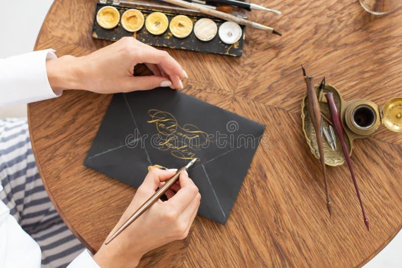 Kvinnakalligrafen rymmer en penna med färgpulver och tecken en bokstav i handskriven stilsort N?rbild slapp fokus Top besk?dar arkivfoton