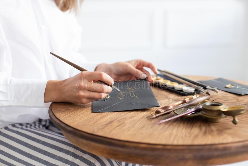 Kvinnakalligrafen rymmer en penna med färgpulver och tecken ett kort i handskriven stilsort N?rbild slapp fokus arkivbilder