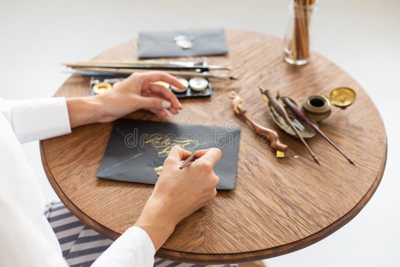 Kvinnakalligrafen rymmer en penna med färgpulver och tecken ett kort i handskriven stilsort N?rbild slapp fokus royaltyfria bilder