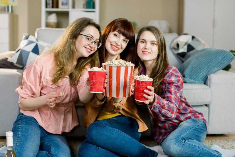 Kvinnakamratskap, hem- parti Tre h?rliga roliga ung flickav?nner med popcorn i h?nder som in sitter p? golvet arkivbild