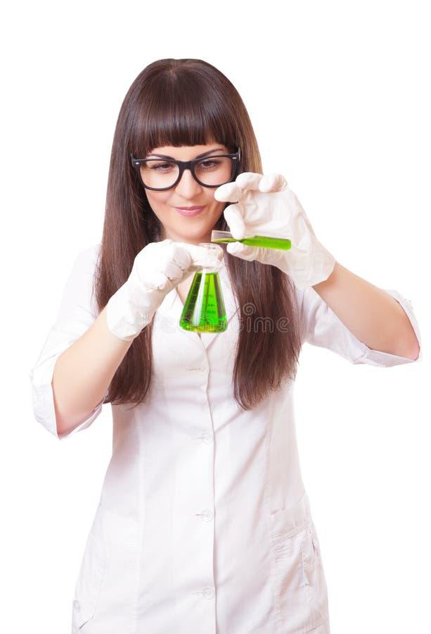 Kvinnakemisten häller flytande från en provrör i flaska royaltyfri fotografi