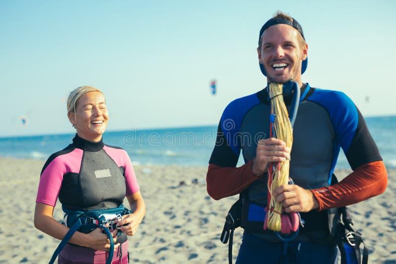 Kvinnakitesurfer som tycker om sommartid på den sandiga stranden med hennes pojkvän royaltyfria bilder