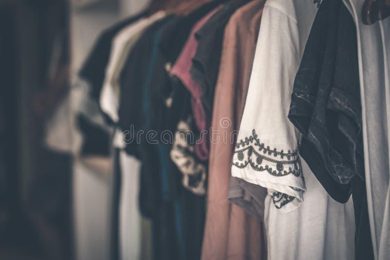 Kvinnakläder som hänger i lagret hissar, exponeringsglas och metall royaltyfri bild