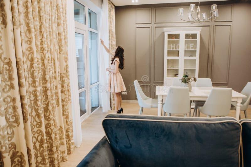 Kvinnaklänning som drömmer inre rum för hus arkivbild