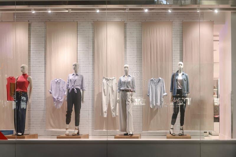 Kvinnaklänningen shoppar fönsterframdelen arkivbilder